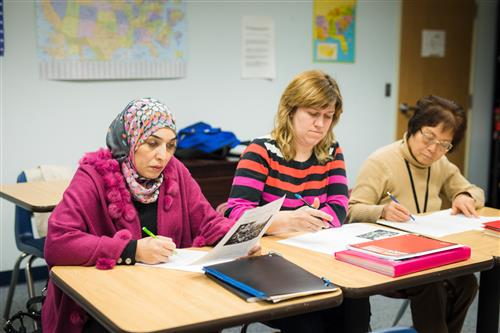 Adult English language learners study in class.