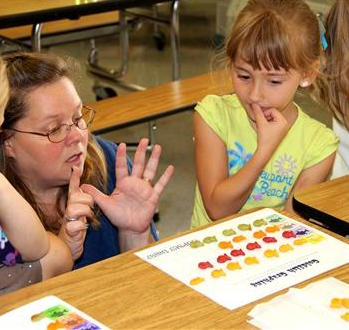 Teacher working with young students on counting.